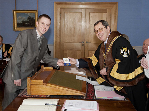 Simon Hughes receives his medal from the Master, David Hamilton, in January 2010