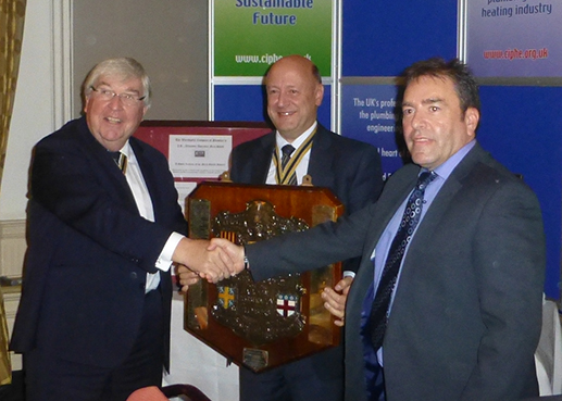 The Master presents the Shield to a tutor from New College Durham